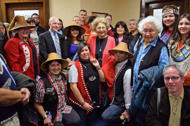 Rep. Jonathan Kreiss-Tomkins (in suit coat and blue shirt) and supporters of House Bill 216 gather in a Capitol hallway for a group photo to celebrate passage of the bill through the House State Affairs Committee, April 1, 2014. The bill would symbolically make 20 Alaska Native languages official state languages alongside English. (Photo by Skip Gray/Gavel Alaska)