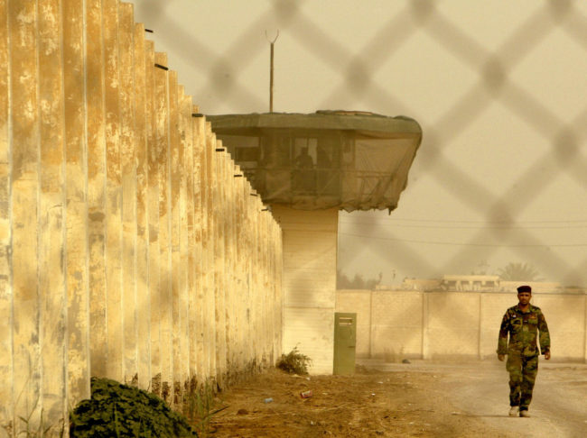 An Iraqi security officer patrols the grounds at Baghdad Central Prison in Abu Ghraib, in 2009. Wathiq Khuzaie/Getty Images