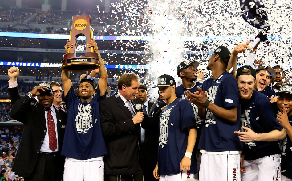 Ryan Boatright of the Connecticut Huskies holds up the NCAA championship trophy after defeating the Kentucky Wildcats 60-54 at AT&T Stadium on Monday, as his teammate Shabazz Napier is interviewed after the game. Jamie Squire/Getty Images