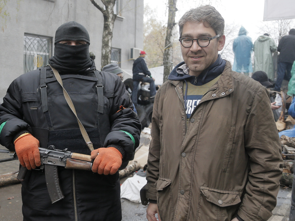 In a photo taken earlier this month, U.S. reporter Simon Ostrovsky stands with a pro-Russian gunman at a seized police station in the eastern Ukrainian town of Slovyansk. Ostrovsky has reportedly been seized by the pro-Russian insurgents. (Efrem Lukatsky/AP)