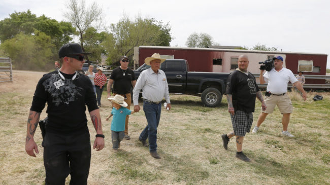 Rancher Cliven Bundy (center) walks with his grandson Braxton Louge along with armed security guards near his ranch house Friday. Bundy's ranch, west of Mesquite, Nev., has become a rallying point for protesters who back his fight against the Bureau of Land Management over grazing fees. George Frey/Getty Images