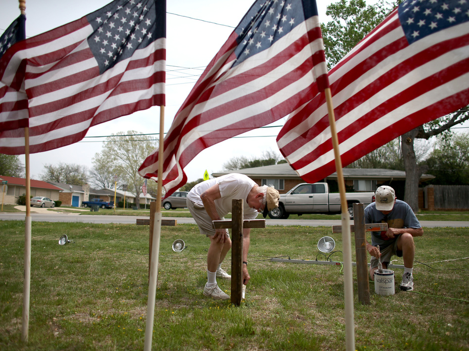 Bob Butler (left) and Bob Gordon paint crosses they placed in front of American flags at Central Christian Disciples of Christ church in the city of Killeen, Texas, which is home to Fort Hood. Joe Raedle/Getty Images