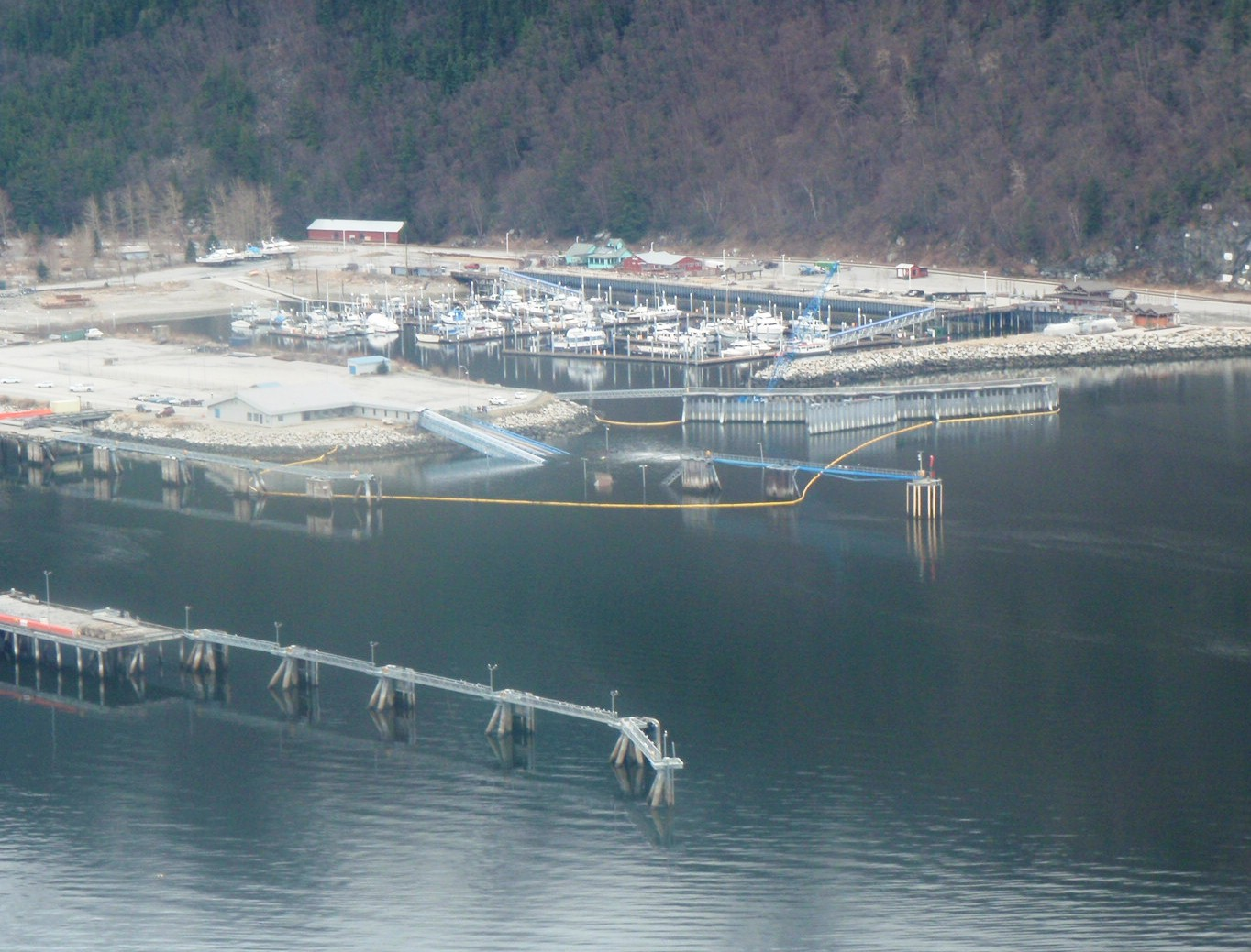 Oil containment boom remains in place around the sunken Skagway ferry terminal dock. (Photo courtesy Kirk Miller, Alaska DOT&PF.