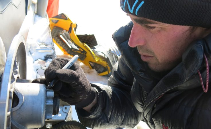Ben Jones of the USGS Alaska Science Center in Anchorage works on a broken snowmachine on a frozen lake not far from the Arctic Ocean. (Photo by Ned Rozell)