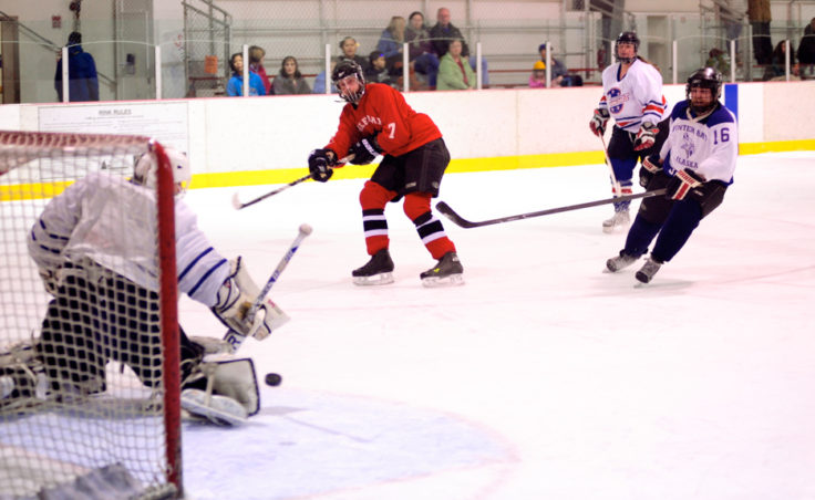 Killer Whales Jason Hort unleashes a shot that Funter Bay goalie Pete Sommers kicks aside in a Tier B title game.