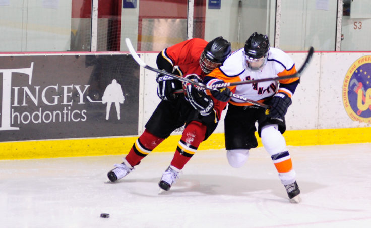 Kensington's Todd Araujo leans into Island Pub's Alec Venechuk in a battle for the puck.