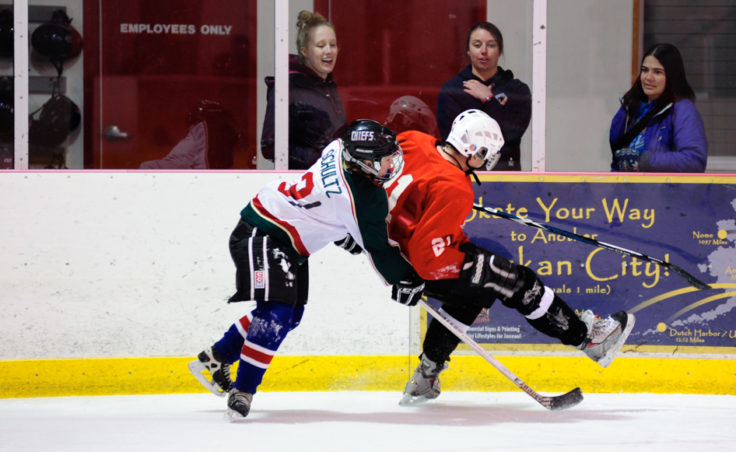 Funter Bay's Caroline Schultz nearly upends Killer Whales' Mike Cooney as they go for the puck along the boards.