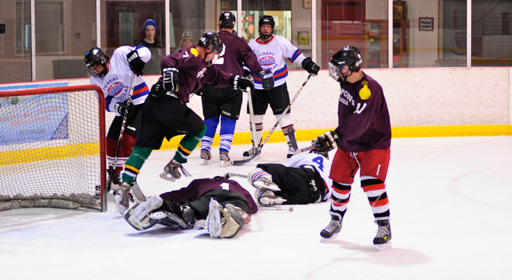 Bodies often fly when things get crowded in front of a net as this scrum illustrates.