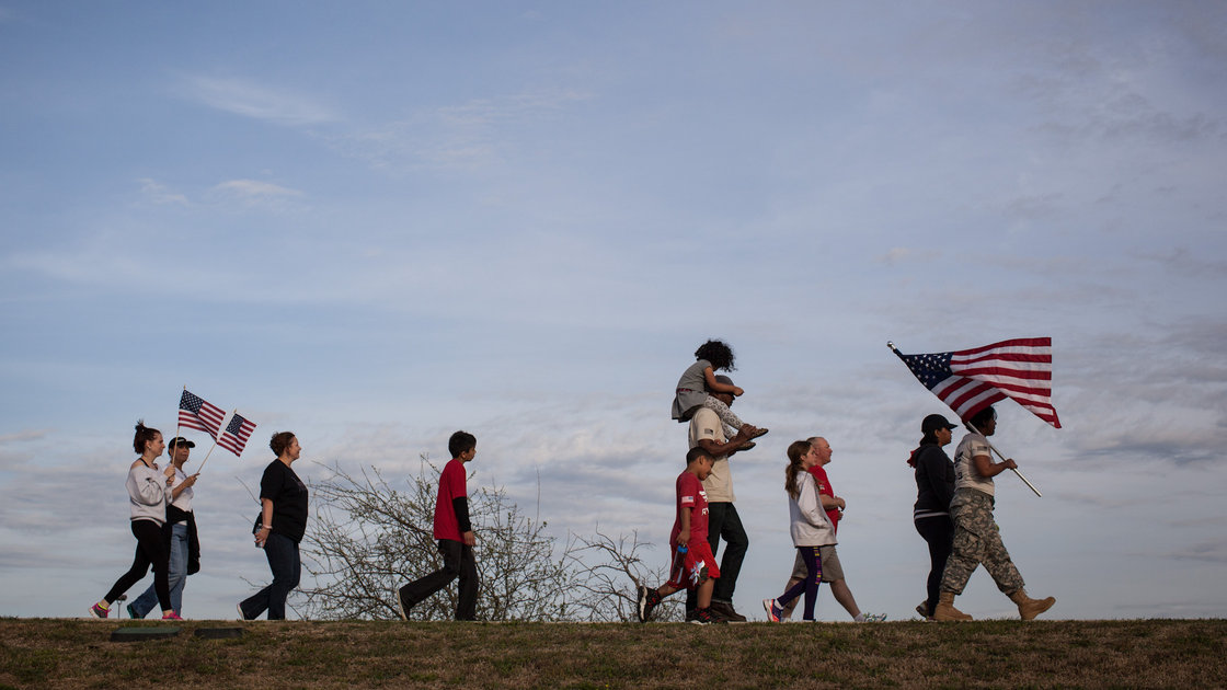 Active members of the military, veterans and civilians march through Lions Club Park to pay tribute to the victims and families affected by the Fort Hood shooting Friday in Killeen, Texas. Tamir Kalifa/AP