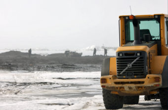 Heavy equipment at the edge of the sea ice in Nome on Monday afternoon. (KNOM photo)