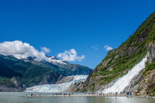 Summer tourists surround Nugget Falls during a visit to Mendenhall Glacier. (Photo by Heather Bryant/KTOO)