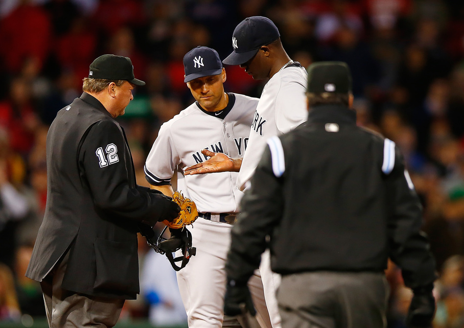 Home plate umpire Gerry Davis checks out the hand of Michael Pineda of the New York Yankees in front of teammate Derek Jeter before throwing him out of the game in the second inning against the Boston Red Sox. (Jared Wickerham/Getty Images)