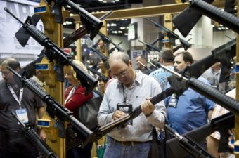 A man examines weapons in the exhibit hall at the 143rd NRA Annual Meetings and Exhibits at the Indiana Convention Center in Indianapolis. Karen Bleier/AFP/Getty Images