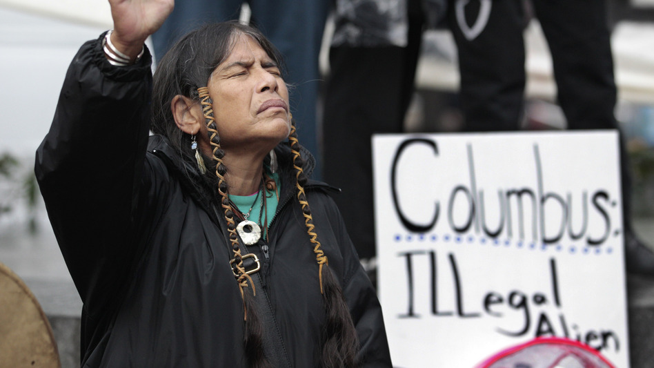 Columbus Day will be designated as Indigenous Peoples Day in Minneapolis, which has become one of several U.S. cities to make the change. Here, a member of the Cowichan Tribes holds her hand up in prayer during a 2011 Native American protest against Columbus Day in Seattle. Elaine Thompson/AP