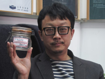 Beijing artist Liang Kegang poses in a Beijing art gallery earlier this week with the jar of fresh air he collected in Provence, France. Didi Tang/AP