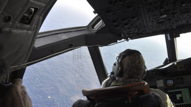 A crewman on a Royal New Zealand Air Force P-3 Orion searches for possible debris from the missing Malaysia Airlines Flight 370, in the southern Indian Ocean earlier this month. Kim Christian/AP