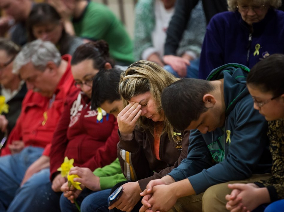 Residents bow their heads during a prayer service Friday at Haller Middle School in Arlington, Wash., that was dedicated to the communities affected by the Highway 530 mudslide. Marcus Yam/AP