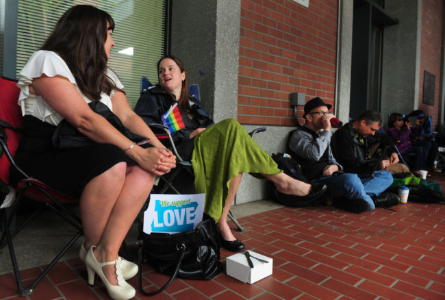 Julia Fraser (from left), Jessica Rohrbacher, Ken Brashier and Andrew Wallace await a ruling in the marriage equality case, so they can go into the building and get their marriage licenses. Steve Dykes /AP