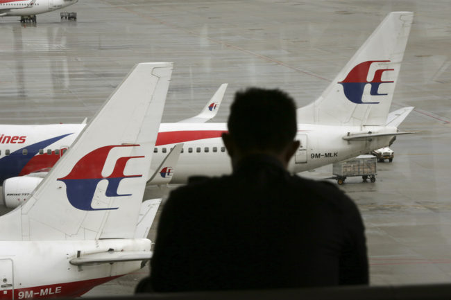 A visitor looks out from the viewing gallery as Malaysia Airlines aircraft sit on the tarmac at the Kuala Lumpur International Airport (KLIA) in Sepang, Malaysia, on May 27, 2014. Vincent Thian/AP