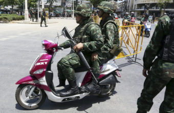 Thai soldiers patrol on a scooter Friday near the Democracy Monument in Bangkok. Thailand's ruling military summoned leaders of the ousted government to meetings today. Restrictions on TV broadcasts have led Thai citizens to ask for more variety. Apichart Weerawong/AP