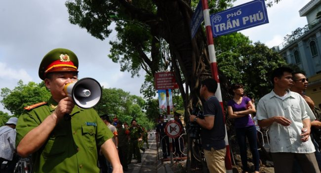 Policemen ask people to leave a street near to the Chinese embassy in Hanoi on Sunday. A call for further anti-China protests appeared to have fizzled in the capital, with authorities deploying heavy security around the Chinese embassy and other suspected protest sites. Hoang Dinh Nam /AFP/Getty Images