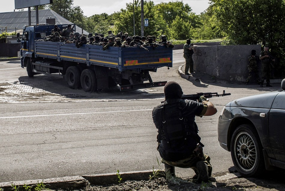 A pro-Russian fighter takes position behind a car as a truck full of rebel fighters heads toward a battle with Ukrainian forces near the airport in Donetsk Monday. The rebels say more than 30 of their number were killed in the violence. Fabio Bucciarelli/AFP/Getty Images