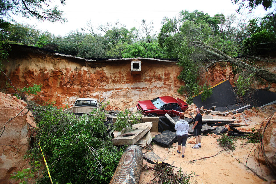 People survey the damage on Scenic Highway in Pensacola, Fla., after part of it collapsed following heavy rains and flash flooding on April 30. Marianna Massey/Getty Images