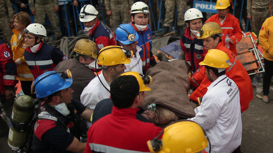 Rescue workers carry a man from the coal mine in Soma, western Turkey, site of a disaster that has killed more than 200 people. Emrah Gurel/AP