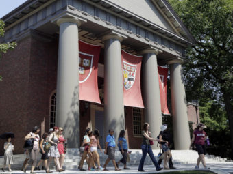 People tour the campus of Harvard University in Cambridge, Mass., in 2012. Harvard was one of 55 institutions on the Education Department's newly released list. Elise Amendola/AP