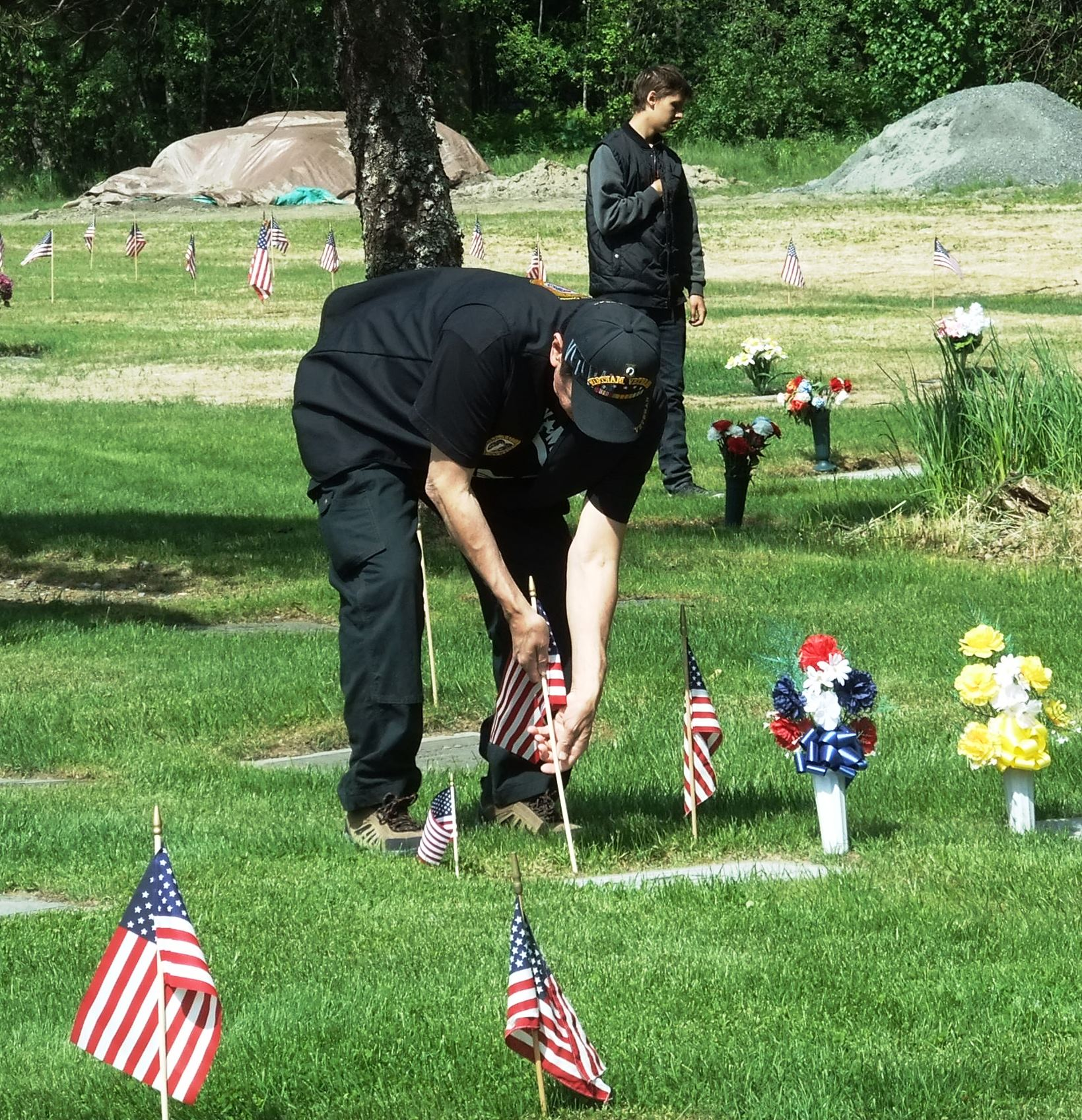 A veteran places a small flag near a grave stone on Memorial Day at Alaskan Memorial Park on Riverside Drive in Juneau. (Photo by Rosemarie Alexander/KTOO)