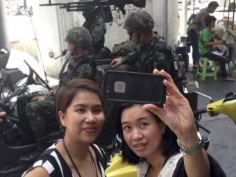 Residents stop to take a photo of themselves at a military checkpoint in central Bangkok on Tuesday. Thailand's army declared martial law in a surprise move it says is aimed at quelling political unrest. Kiko Rosario/AP
