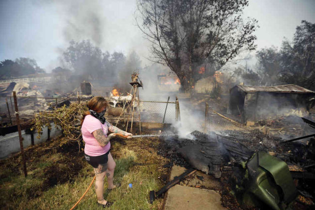 A woman douses debris around her home as her neighbor's home burns Thursday in Escondido. One of the nine wildfires burning in San Diego County suddenly flared Thursday afternoon and burned close to homes, triggering thousands of new evacuation orders. Gregory Bull/AP