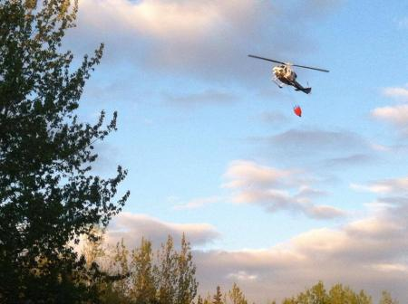 A helicopter drops water on the fire near Soldotna Monday night (Photo by Ariel Van Cleave)