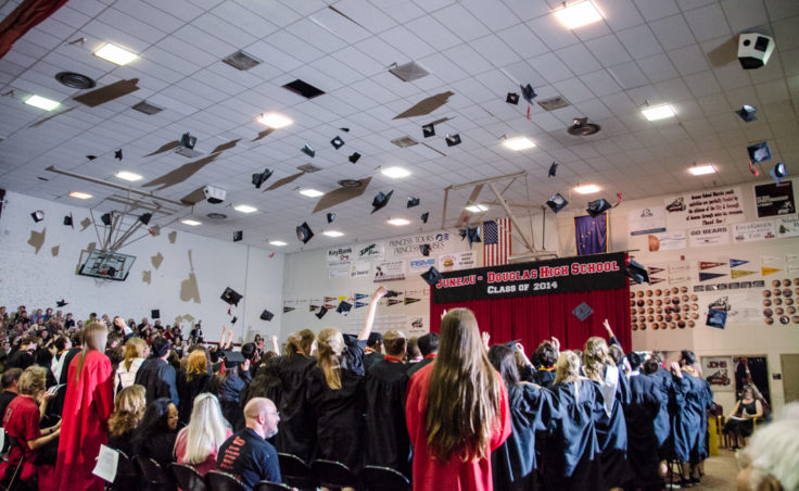 Graduates throw their caps into the air after receiving their diplomas. Rap music played as the students left the gym. (Photo by Heather Bryant/KTOO)