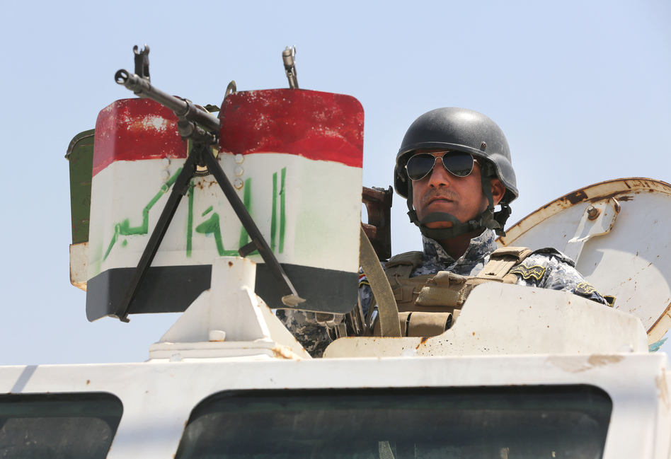 An Iraqi federal policeman standing on top an armored vehicle secures a checkpoint in Baghdad, Iraq, on Sunday. Karim Kadim/AP