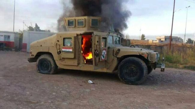 A cellphone photo shows an armored vehicle belonging to Iraqi security forces in flames Tuesday, after hundreds of militants launched a major assault in Mosul. Some 500,000 Iraqis have fled their homes in the large city since militants took control. AFP/Getty Images