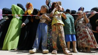 Displaced Iraqi children line up with their mothers Tuesday to register at a temporary camp for people fleeing violence in northern Iraq. Karim Sahib/AFP/Getty Images