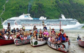 The paddlers pose as a cruise ship goes by Sandy Beach. (Photo by Ed Schoenfeld/CoastAlaska News)