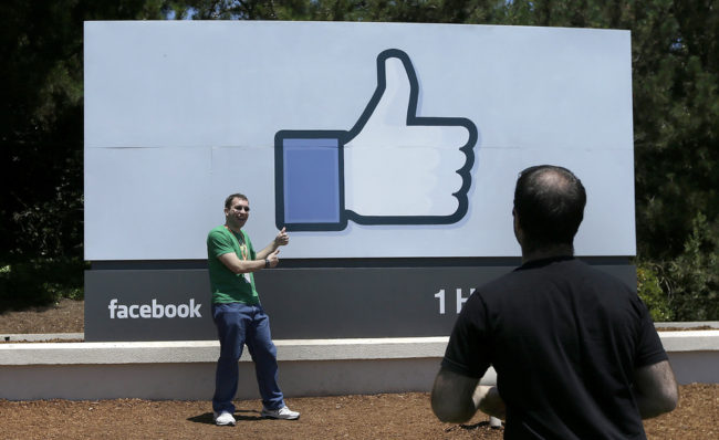 A man poses for photographs in front of the Facebook sign on the Facebook campus in Menlo Park, Calif. Jeff Chiu/AP