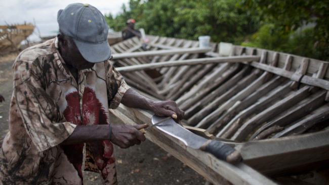 In Leogane, Haiti, a boat-maker sharpens his machete. The 30-foot-long boats are purchased by smugglers for around $12,000 and then taken to northern Haiti to find passengers. Dieu Nalio Chery/AP