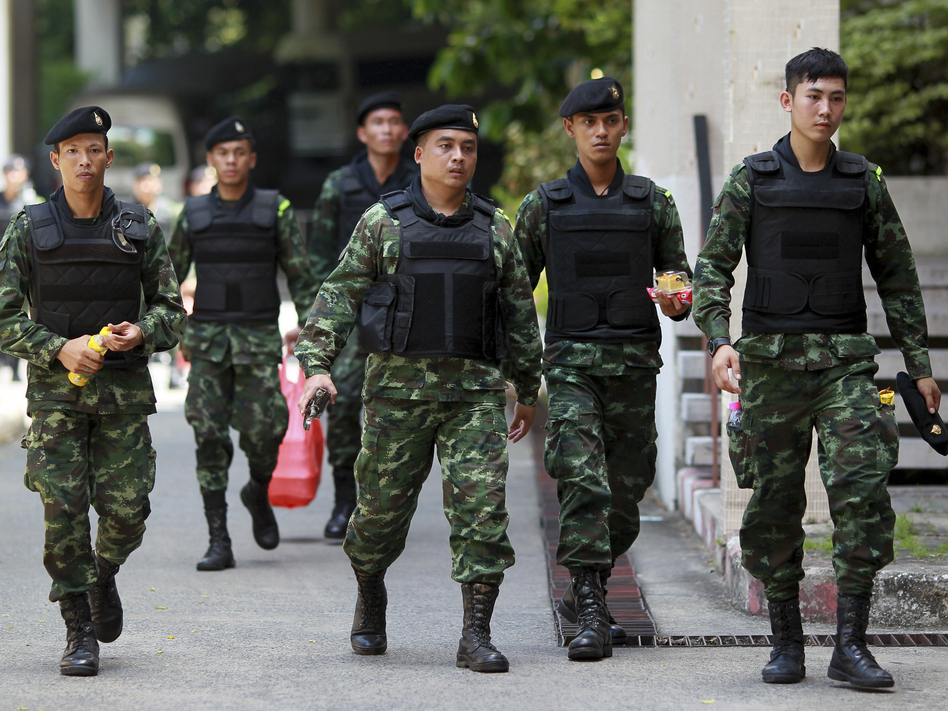 Thai soldiers walk after being deployed to guard Bangkok's Victory Monument against anti-army protests, on Sunday. The ruling junta is now insisting that foreign journalists not call the military takeover a coup. Wason Wanichakorn/AP