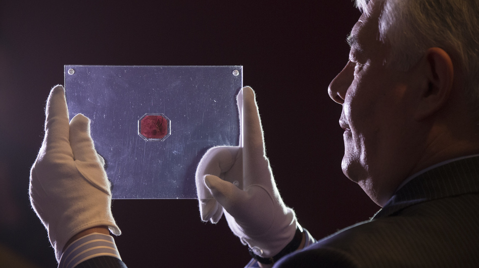 "David Redden of Sotheby's auction house holds a case containing the sole-surviving ""British Guiana One-Cent Black on Magenta"" stamp dating from 1856. Oli Scarff/Getty Images"
