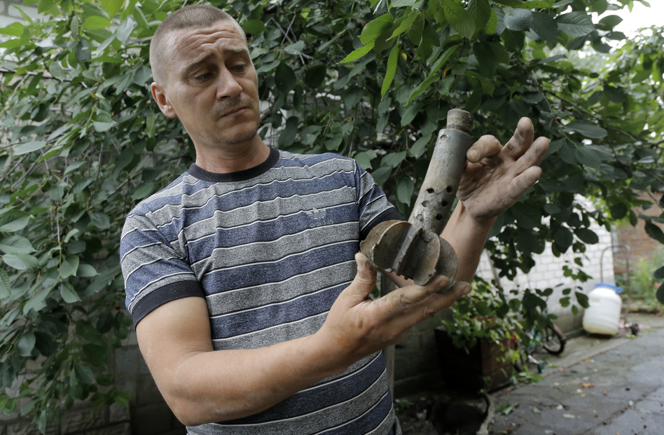 A man who lives in Ukraine's Donetsk region shows part of a shell that exploded in the yard of his house Wednesday, after a reported mortar attack by Ukrainian government forces Tuesday. The area is under a tense ceasefire that will expire Friday. Dmitry Lovetsky/AP