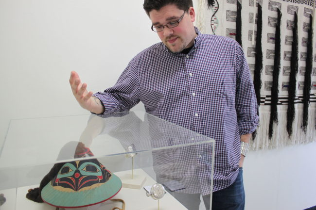 "Juror David R. Boxley points out the beauty in Wayne Price's ""Dancing Raven Hat,"" which Boxley awarded the competition's highest honor Best of Show. (Photo by Lisa Phu/KTOO)"