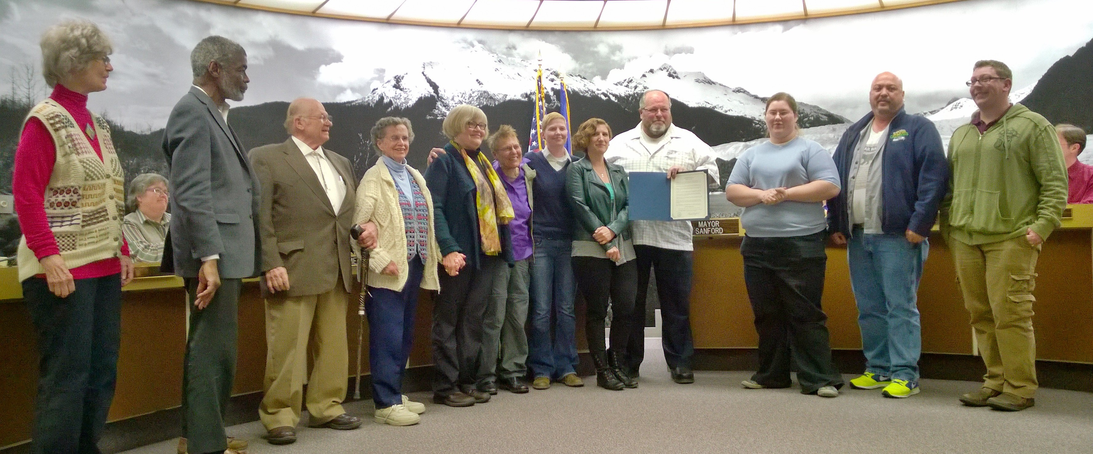 Supporters pose with Mayor Merrill Sanford after he read a proclamation declaring June 2014 as Juneau Pride 2014. It's a celebration of LGBT people and their contributions. (Photo by Jeremy Hsieh/KTOO)