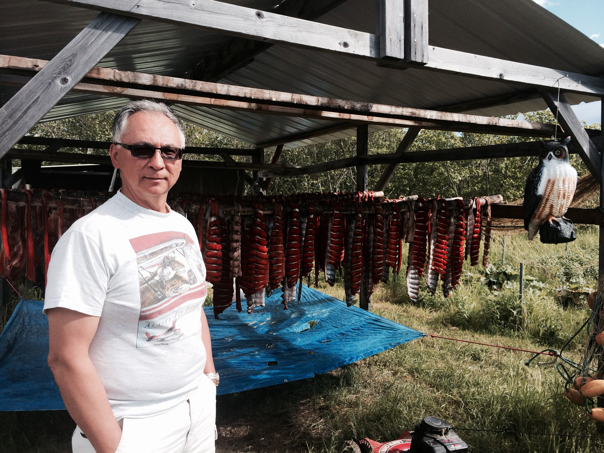 Arvin Dull, of Bethel, with his drying salmon at his fish camp in Oscarville Slough. (Photo by Daysha Eaton/KYUK)
