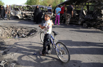 An Iraqi boy and other civilians look at the aftermath of a car bomb in Baghdad's Sadr City on Wednesday. The violence in the Shiite district comes as Sunni militants advance in northern Iraq. Karim Kadim/AP