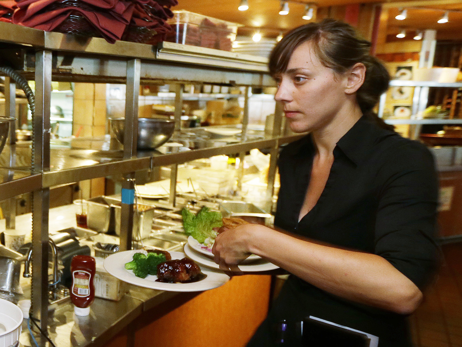 Seattle waitress Wendy Harrison picks up a lunch order on Monday. She stands to be affected by a $15 minimum wage approved by the Seattle City Council. Ted S. Warren/AP
