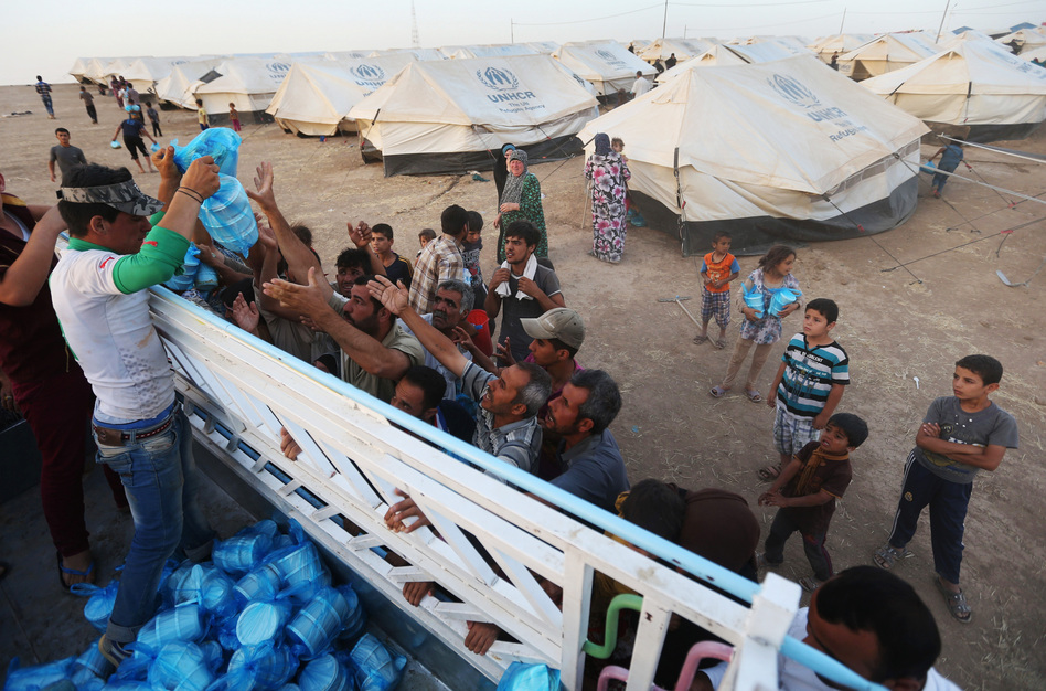 Displaced Iraqi citizens receive meals to break their Ramadan fast from a Kurdish charity group. Iraq's central government has launched its first major operation against the ISIS insurgent group. Hussein Malla/AP