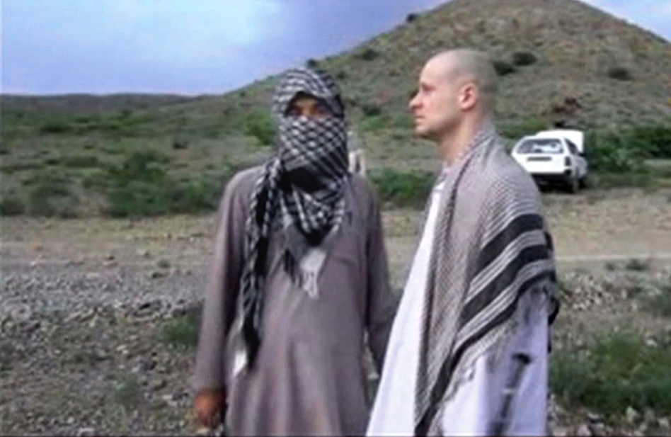 In this file image taken from video obtained from Voice Of Jihad Website, which has been authenticated based on its contents and other AP reporting, Sgt. Bowe Bergdahl (right) stands with a Taliban fighter in eastern Afghanistan. AP